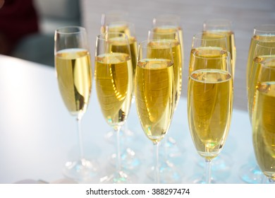 Glasses with champagne on the party table. lot of alcohol. Glasses of champagne on a white table