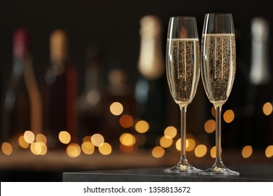 Glasses of champagne on table against blurred background. Space for text