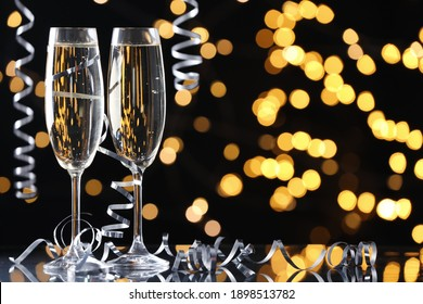 Glasses of champagne and serpentine streamers against black background with blurred lights. Space for text