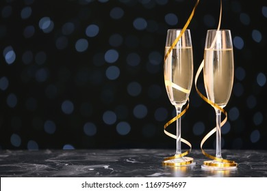 Glasses with champagne and space for text against blurred Christmas lights