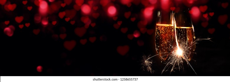 Glasses of champagne with sparkler and red bokeh for valentines day
