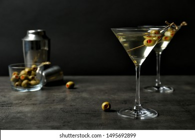 Glasses of Classic Dry Martini with olives on grey table against black background