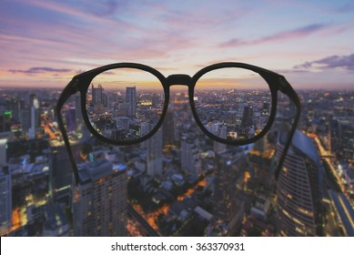 Glasses with clear vision of night cityscape focused