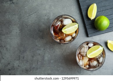 Glasses of cocktail with cola, ice and cut lime on grey background, flat lay. Space for text