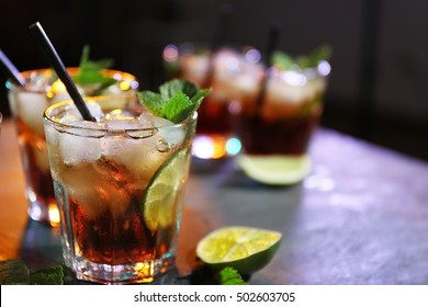 Glasses of cocktail with ice on dark background