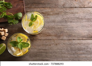 Glasses of cocktail with lemon and mint on wooden background