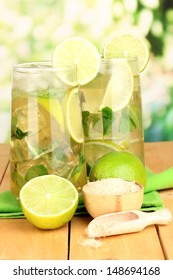 Glasses of cocktail with lime and mint on wooden table on bright background