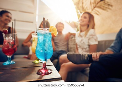 Glasses of cocktail on table with young people sitting on sofa on roof top. Friends having a rooftop party.
