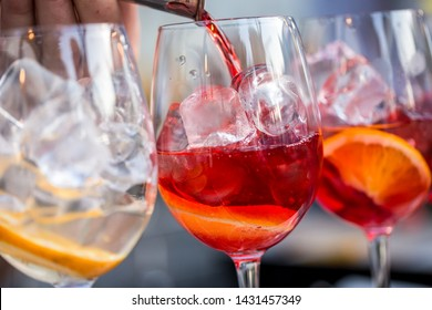 glasses of cocktails on the bar. bartender pours a glass of sparkling wine with red alcohol.