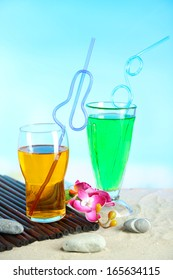 Glasses of cocktails on sand, on bright background