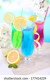 Glasses of cocktails on table on light blue background
