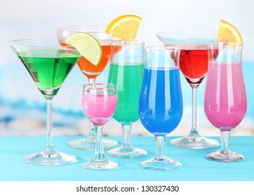 Glasses of cocktails on table near pool