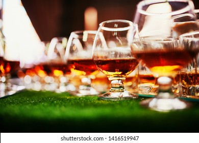 glasses with cognac, whiskey stand on the bar. a lot of glasses with cognac. alcohol in the glasses. Various alcohol drinks standing on bar. glasses with cognac on the bar