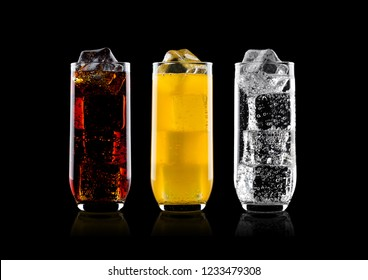 Glasses of cola and orange soda drink and lemonade sparkling water on black background with ice cubes