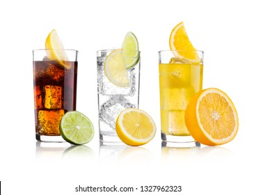 Glasses of cola and orange soda drink and lemonade sparkling water on white background with ice cubes lemons and lime bits