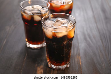 Glasses of cold cola on wooden table