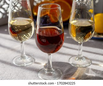 Glasses with cold dry fino and sweet cream sherry fortified wine and orange in summer sunlights, andalusian style interior on background