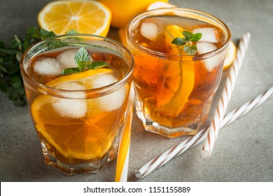 Glasses of cold ice tea with lemon, ice, mint on background. Homemade lemonade. Spring and summer drinks and beverages concept.
