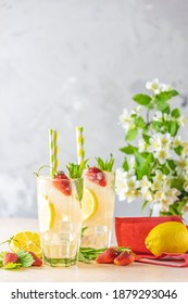 Glasses of cold icy refreshing drink with lemon and strawberry served on light pink table. Fresh cocktail drinks with ice fruit and herb decoration