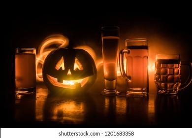 Glasses of cold light beer with pumpkin on a wooden table for Halloween. Glasses of fresh beer and pumpkin on a dark toned foggy background