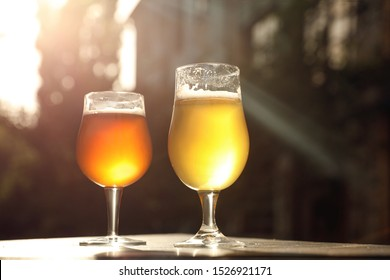 Glasses of cold tasty beer on wooden table outdoors