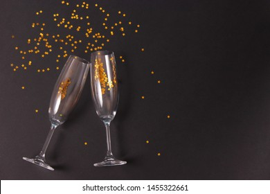 glasses and confetti on a colored background top view.