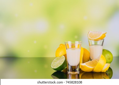 Glasses of cream liqueur with lime and lemon on green background with reflection. Shot of lemon liqueur. Traditional Italian alcoholic beverage Limoncello