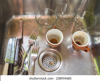 Glasses, cups and cutlery inside the stainless steel washbasin