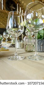 Glasses and cutlery on a restaurant table in a bright scenery