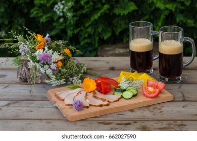 ?wo glasses of dark beer and ham, cheese and vegetable plate on wooden background. Midsummer in Latvia. Celebration of traditional Ligo feast in june