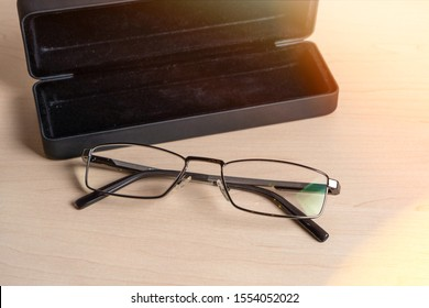Glasses and a dark blue case on a light wooden table. Eyeglass storage and care