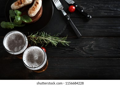 Glasses of delicious beer with grilled sausages and herbs on wooden table