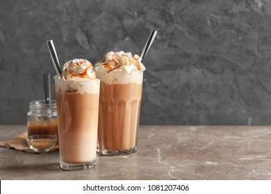 Glasses with delicious caramel frappe on table