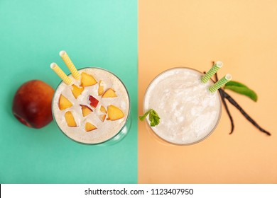 Glasses with delicious milk shakes on color background, top view