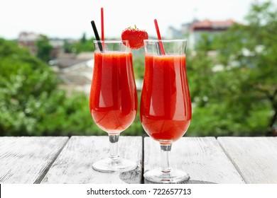 Glasses of delicious strawberry daiquiri on table