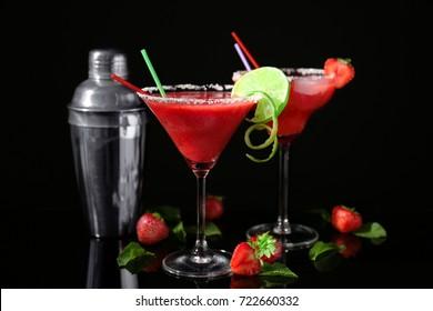 Glasses of delicious strawberry daiquiri on black background