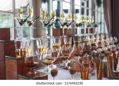 Glasses with different alcohol coktails and beverages stand on the table