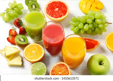 Glasses with different juices and fresh fruits on wooden table
