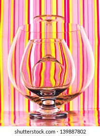 Glasses of different sizes standing straight and overturned on colorful striped background