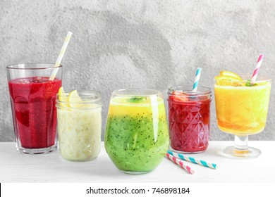 Glasses with different smoothies on table against color background
