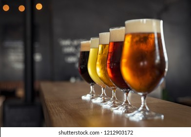 Photo of Glasses with different sorts of craft beer on wooden bar. Tap beer in pint glasses arranged in a row. Closeup of five glasses of different types of draught beer in a pub.