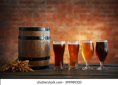 Glasses with different sorts of craft beer, wooden barrel and barley ears on brick wall background