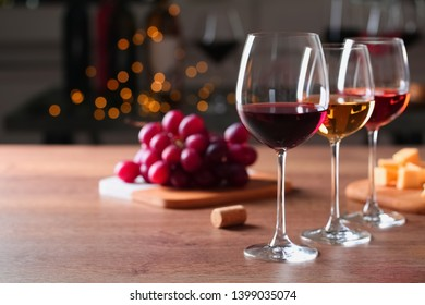 Glasses with different wines and appetizers on wooden table against blurred background. Space for text