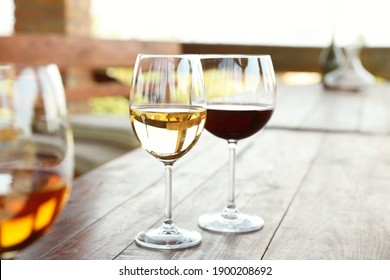 Glasses with different wines on wooden table in outdoor cafe