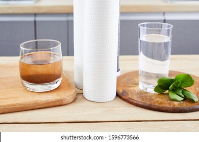 Glasses of dirty and clear water and filter cartridges to domestic water osmosis systems at modern kithen background. Concept of water filtration.