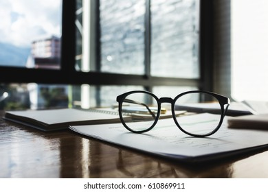Glasses with documents on the table of business people.