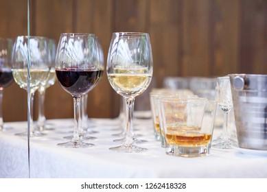 Glasses of elite red and white wine, martini, and ice bucket on a festive table.