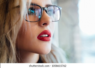 Glasses eyewear woman portrait looking away. Close up portrait of female business beautiful student woman model face. Blonde, red lips. Indoor.