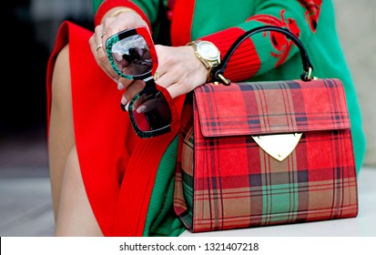 Glasses in female hands. Bag close up. Scottish plaid bag. Stylish modern and feminine image, style. Women's accessories: watches, glasses. red and green