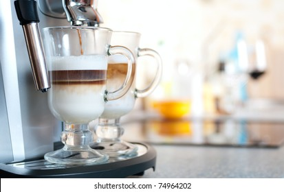 Glasses filled with cappuccino in coffee machine on kitchen